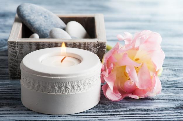 Kerze und kieselsteine auf holz
