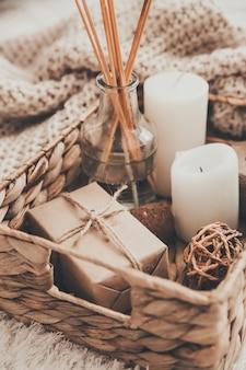 Kerze und strickkleidung im weidenkorb