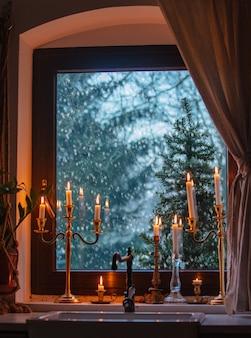 Kerzen am fenster in der küche während eines schneefalls