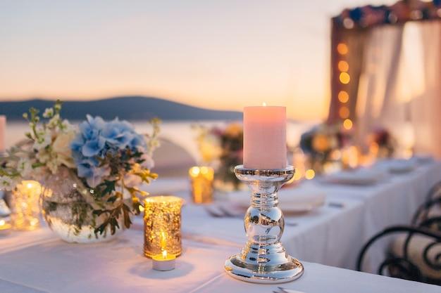 Kerzen auf dem hochzeitstisch bei einem bankett