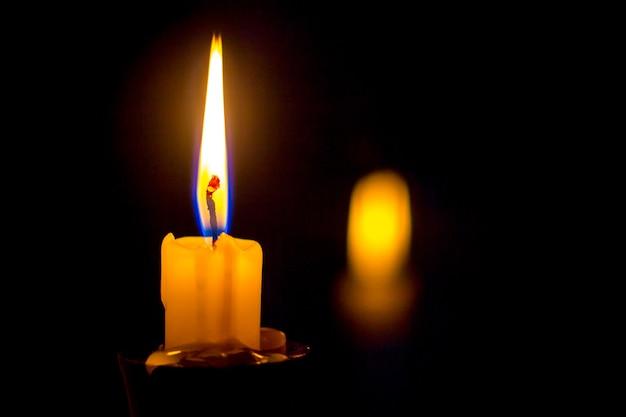 Kerzen auf kerzenhalter, die mit hellem feuer auf einem schwarzen hintergrund verbrennen