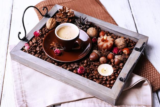 Kerzen auf vintage-tablett mit kaffeebohnen und gewürzen, tasse tee cup