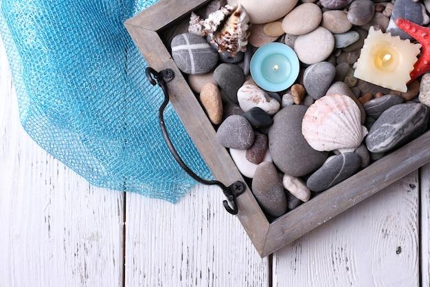 Kerzen auf vintage-tablett mit kieselsteinen, seesternen und muscheln auf holzhintergrund