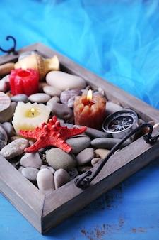 Kerzen auf vintage-tablett mit kieselsteinen, seesternen und muscheln auf holzoberfläche