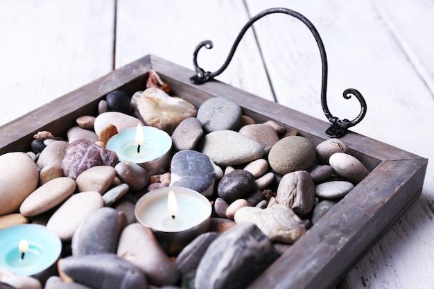 Kerzen auf vintage-tablett mit meerkieseln,