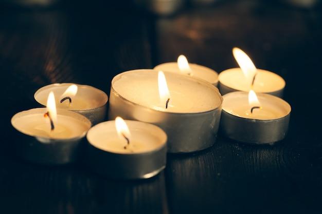 Kerzen brennen in der dunkelheit über schwarz. gedenken.