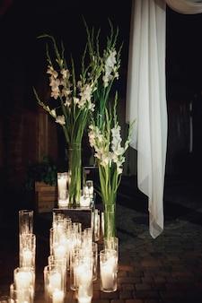 Kerzen brennen in hohen vasen auf dem boden Kostenlose Fotos