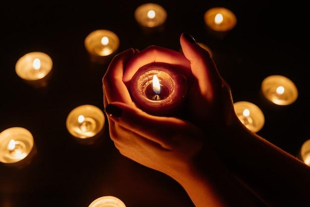 Kerzen brennen. kerze in weiblichen händen. viele kerzen brennen nachts. viele kerzenflammen leuchten.
