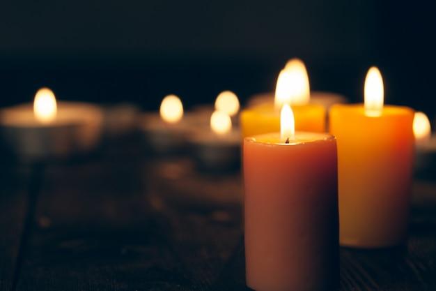 Kerzen, die in der dunkelheit über schwarzem hintergrund brennen