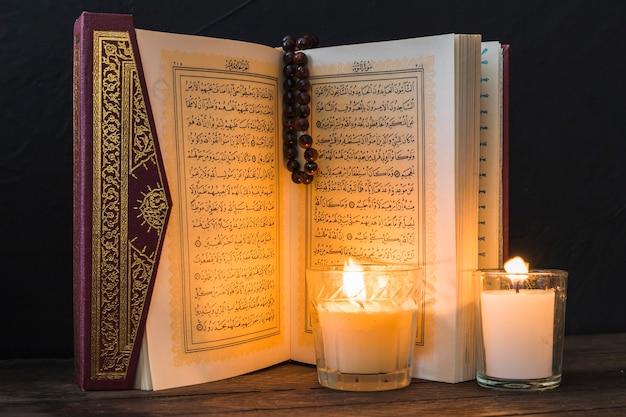 Kerzen, die seiten des geöffneten korans beleuchten