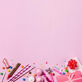 Kerzen; edelsteine; strohhalm; sträusel; geschenkbox; streamer; aalaw unten auf rosa hintergrund