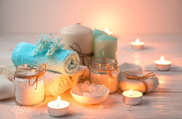 Kerzen, handtücher, seife und salz auf dem hintergrund brennender kerzen.