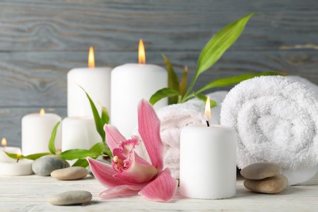 Kerzen, handtücher, steine und orchideen auf holztisch