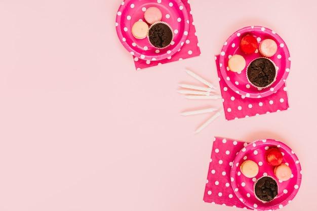 Kerzen in der nähe von tellern mit desserts