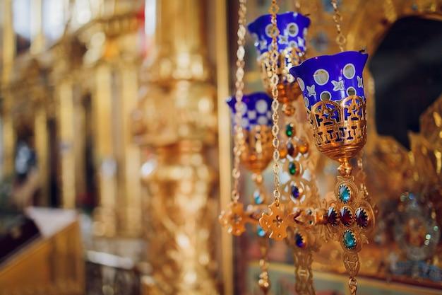 Kerzen in einem katholischen tempel anzünden. in einem katholischen tempel werden in der nähe des altars kerzen angezündet.