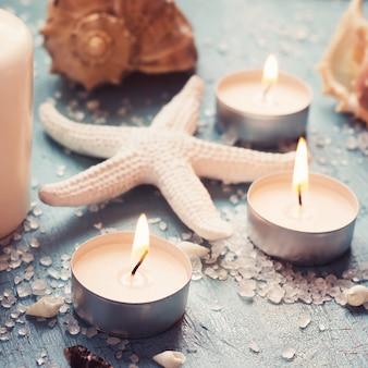 Kerzen, muscheln und seesterne auf einem blauen hintergrund, getönt
