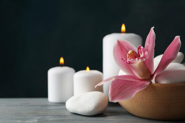 Kerzen, orchideen und steine auf holztisch