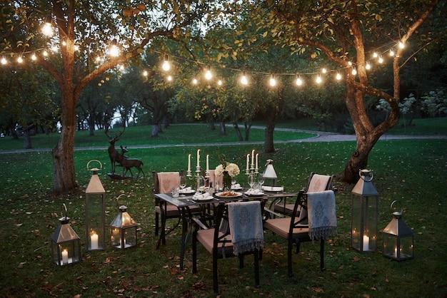 Kerzen- und hirschstatue. vorbereiteter schreibtisch, der auf essen und besucher wartet. abendzeit