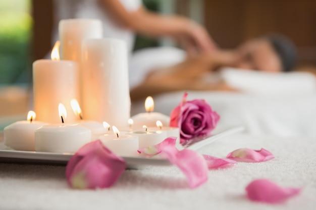 Kerzen und rosenblüten auf massagetisch