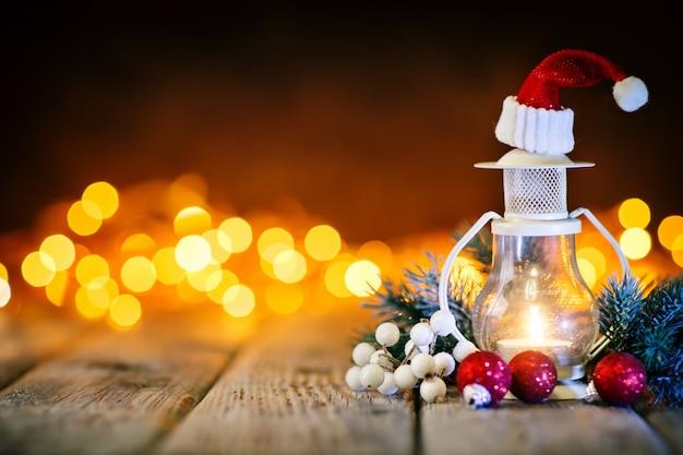 Kerzen- und weihnachtsbälle auf einem holztisch auf dem hintergrund einer girlande. bokeh. .
