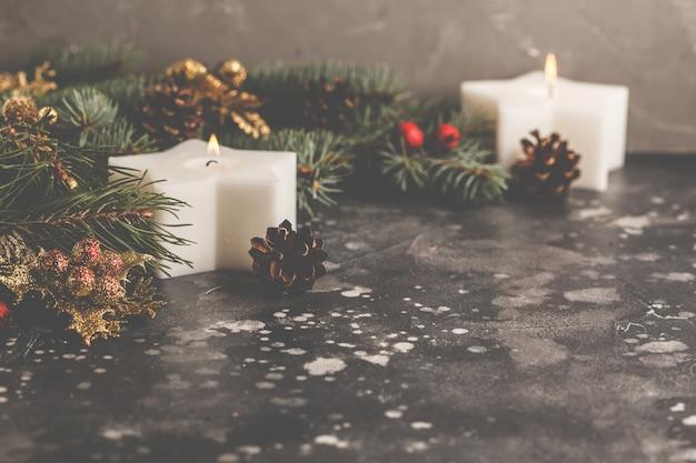 Kerzen und weihnachtsbaum auf einem grauen hintergrund.