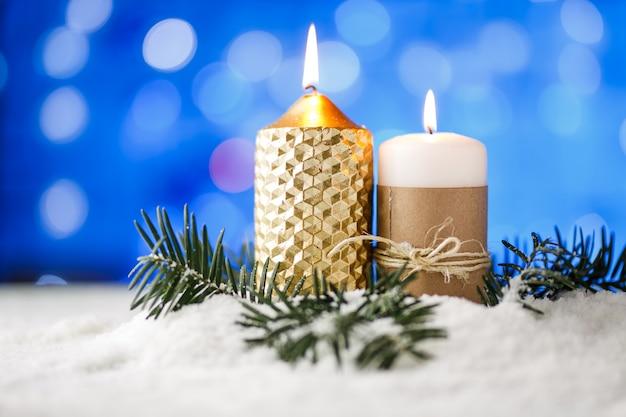 Kerzen- und weihnachtsdekoration im schnee mit blauem lichthintergrund.