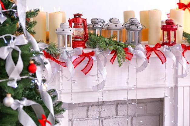 Kerzen und weihnachtsschmuck auf dem kaminsims im zimmer