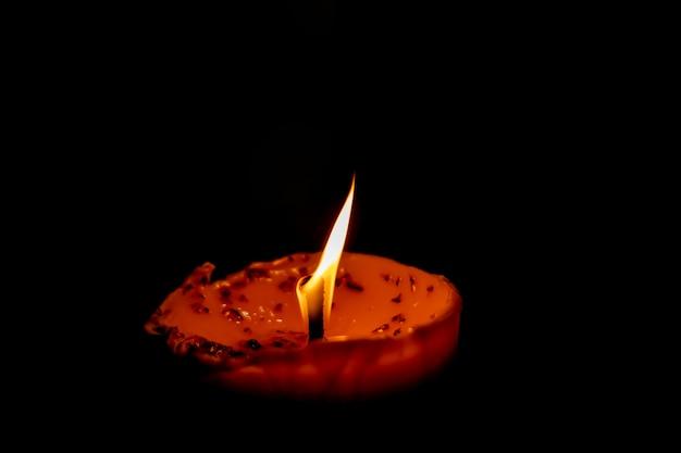 Kerzenflamme gegen lokalisiert auf schwarzem hintergrund