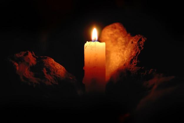 Kerzenflamme mit lichtreflexion auf einem stein