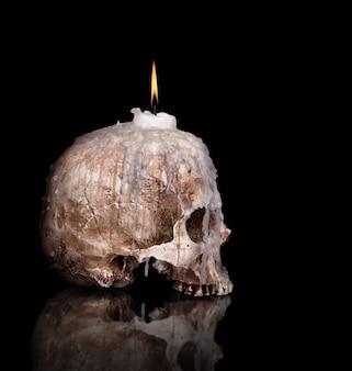 Kerzenhalter vom menschlichen schädel lokalisiert auf schwarz