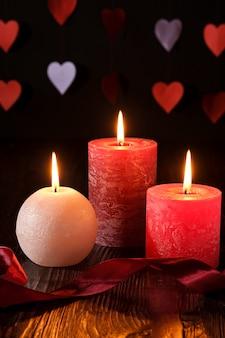 Kerzenlicht mit drei wachsflammen mit band im dunklen romantischen licht auf herzen
