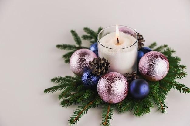 Kerzenlichter mit kugeln, weihnachtsbaum und tannenzapfen