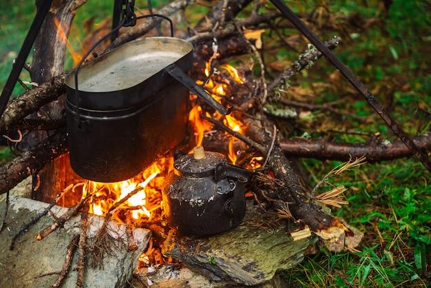 Kessel auf stativ über lagerfeuer. kochen von lebensmitteln auf die natur. abendessen im freien. brennholz, zweige und reisig im feuer. aktive erholung. camping. atmosphärisches feuer.