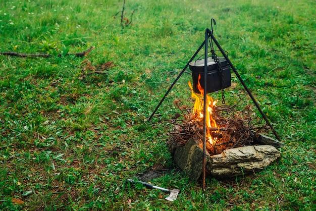 Kessel auf stativ über lagerfeuer.