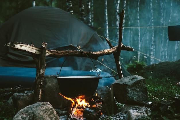 Kessel brennt in der nähe von zelt im wald in der nacht. schönes lagerfeuer im touristenlager in wild. überleben in der taiga. kessel über dem lagerfeuer. rauch vom feuer zwischen bäumen. am lagerfeuer kochen.