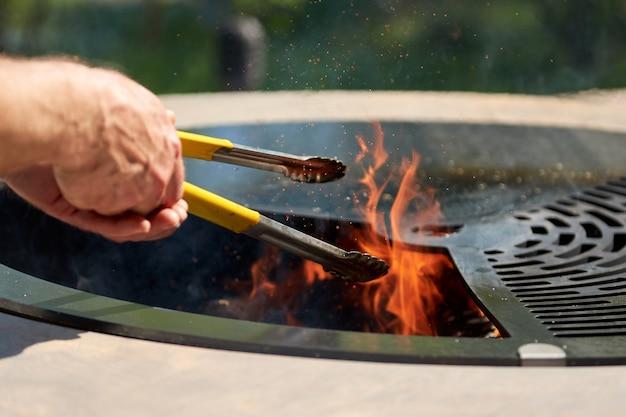 Kesselgrillgrube mit gusseisenrost mit flammen runder tischkochfläche heißer grill auf hinterhof
