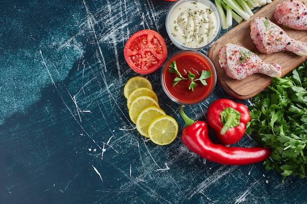 Ketchup- und mayonnaise-saucen mit kräutern und rohen hähnchenschenkeln.