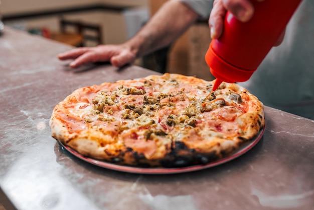 Ketchup zu leckerer pizza geben.