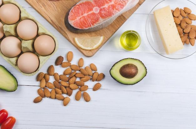 Keto-diät. gesundes essen mit wenig kohlenhydraten. avocado, fisch, öl, nüsse auf weiß