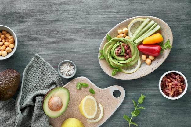 Keto-diät, nahaufnahme von avocado-rose mit speckwürfeln und geräuchertem käse, gewürzt mit zitrone, minzblatt und meersalz