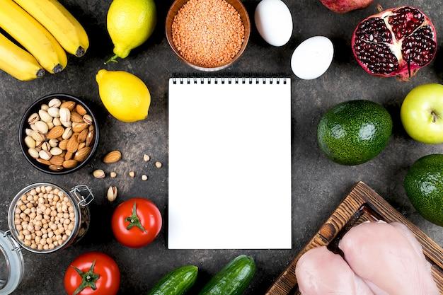 Keto-diät-nahrungsmittelkonzept. fleisch, rohes gemüse, nüsse und früchte auf schiefertischhintergrund. draufsicht, kopierraum. mit notizbuch.