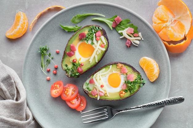 Keto-diätgericht: avocado-boote mit schinkenwürfeln, wachteleiern und käse, top lay