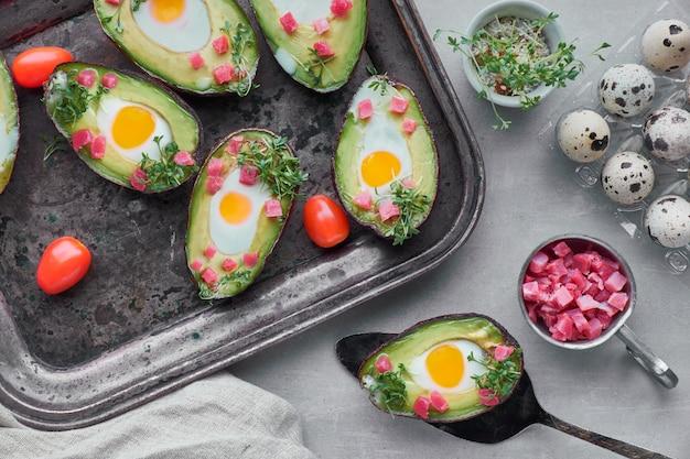 Keto-diätgericht: avocado-boote mit schinkenwürfeln, wachteleiern und tomaten