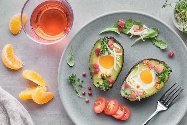 Keto-diätgericht: avocadoboote mit schinkenwürfeln, wachteleiern und käse