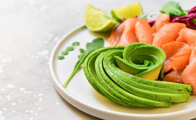 Keto diätkost lachs-avocado-salat mit rucola und limette. keto-essen