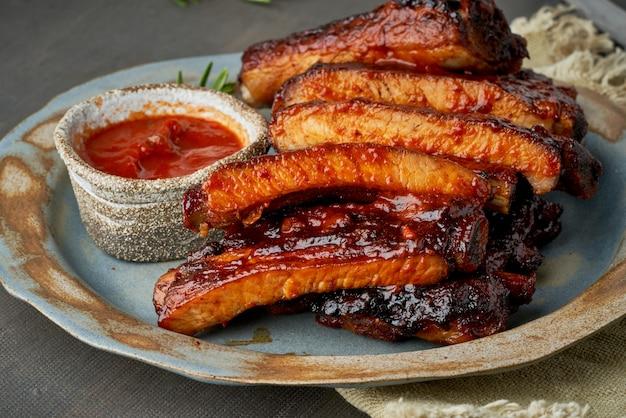 Keto-essen, würzige barbecue-schweinerippchen. langsames kochrezept. eingelegtes gebratenes schweinefleisch mit roter sauce