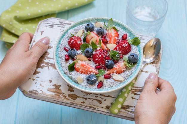 Keto ketogen, paläo low carb diät nicht haferflocken frühstücksbrei. kokos-chia-pudding mit beeren, granatapfelkernen und mandeln