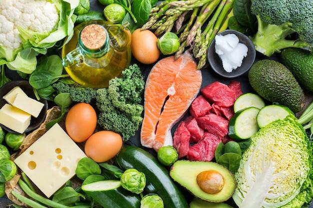 Keto-konzept für ausgewogene ernährung. auswahl an gesunden ketogenen kohlenhydratarmen lebensmittelzutaten zum kochen auf einem küchentisch. grünes gemüse, fleisch, lachs, käse, eier. hintergrund der draufsicht