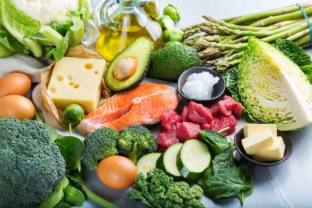 Keto-konzept für ausgewogene ernährung. auswahl an gesunden ketogenen kohlenhydratarmen lebensmittelzutaten zum kochen auf einem küchentisch. grünes gemüse, fleisch, lachs, käse, eier