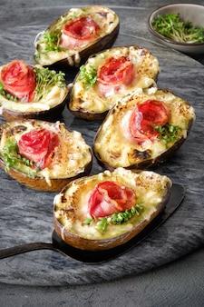 Ketodiätgericht: avocado-boote mit knusprigem speck, geschmolzenem käse und kressesprossen auf dunkelheit